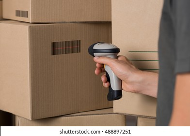 Courier scanning cardboard box with barcode scanner in warehouse. Close up of warehouse manager hand scanning boxes with barcode reader. Man reading and scanning labels on boxes.