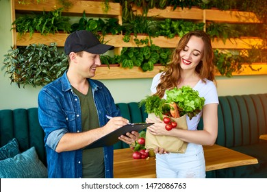 Courier service worker delivering fresh food, giving shopping bag to a happy woman client on the kitchen at home. Online grocery shopping from the internet - shop