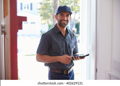 Courier Standing At Front Door With Digital Tablet