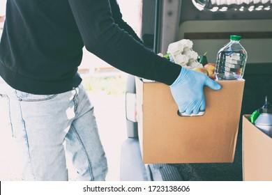 Der Kurier nimmt die Karton-Öko-Box mit Produkten aus dem Lebensmittelgeschäft aus dem Lieferwagen