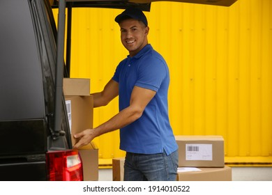 Courier taking parcel from delivery van outdoors