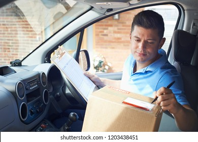 Courier In Van With Clipboard Delivering Package To Domestic House