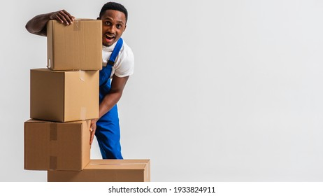 courier, a young African-American in a blue jumpsuit and white T-shirt, tired, standing near the paper boxes folding them, working. Isolated on white background. The concept of delivery, mail, deliver