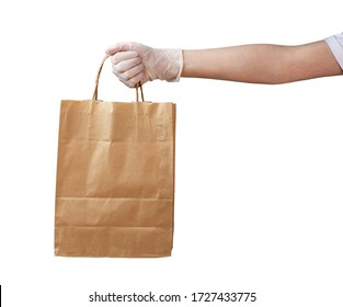 Courier's hand in a medical glove holds a paper bag. Safe delivery by courier to your home, quarantine, stay safe. Isolated on a white background.