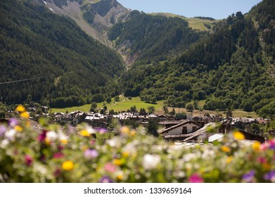 Courmayur, Aosta Valley (Valle d'Aosta), Italy, framed by blurred flowers.