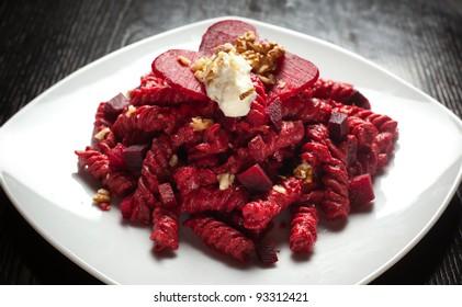 a course of pasta with red beets a dollop of gorgonzola cheese and a sprinkle of crushed walnuts on top. Served on a white dish over a black table