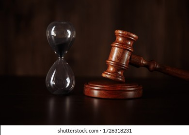 Court concept. Hourglass and judge gavel on table close up