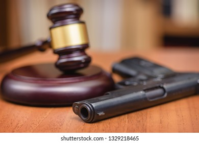 Court for the illegal use of weapons. Sentence for murder. Judge's gavel on wooden table. Judge, hammer, pistol on wooden background.Selective focus.