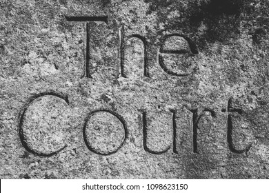 The Court Word Carved In Stone, shallow depth of field black and white high contrast photography