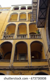 courtryard of an old palace, in typical yellow color,  in the historical center of Naples