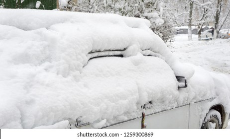 Courtyard after heavy snowfall. The car, covered with thick layer of snow. Right side of a luxury car covered with snow