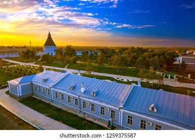 The courtyard with alleys and footpaths of the park during a bright yellow sunset orange sun in the evening at dusk. Historical and architectural complex Astrakhan Kremlin, Russia - September 2014.
