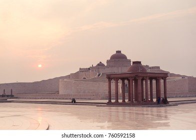 Courtyard of Ambedkar park shot against the setting sun. A multi pillar canopy and the main dome of the Ambedkar Stupa is clearly visible