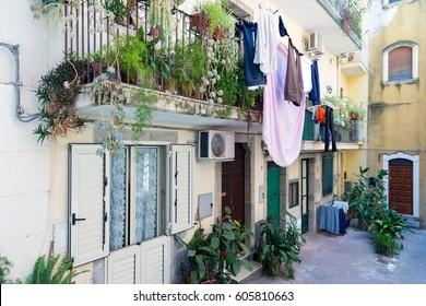 Courtyard with balcony, plants and laundry in Taormina at Sicilian Island, Italy