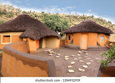 Courtyard of the Basotho tribe village. Round clay huts called rondavels with the straw roof. The local lifestyle. Drakensberg mountains background. Traditional African houses among the wild nature.