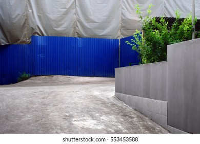 A courtyard of a house covered by a tent due to reconstruction. Objects are almost gray but the house is surrounded by a blue fence. A few small trees nestles in the yard. Russia, Moscow, July 2016.