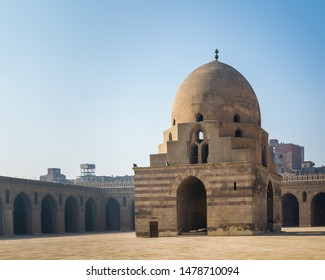 Courtyard of Ibn Tulun public historical mosque with ablution fountain and arched passages surrounding the courtyard in the background, Sayyida Zaynab district, Medieval Cairo, Egypt