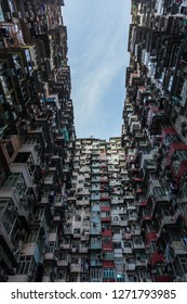 In the courtyard of the monster house in Hongkong with a dramatic view on the house walls with many windows in a crowded city with laundry hanging out the window in portrait format