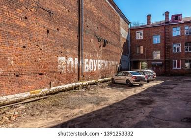 "The courtyard of an old brick apartment building abandoned since Great Patriotic War (1941-1945) (World War II). Inscription in Russian: ""Shelter"". Rybinsk, Yaroslavl region, Russia"