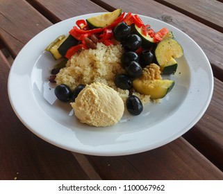 couscous (aka seksu or kuskus) traditional berber North African steam cooked dish of durum wheat semolina granules with vegetables, black Greek olives and hummus