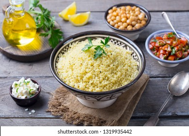 Couscous in bowl with olive oil. Wooden background. Close up.