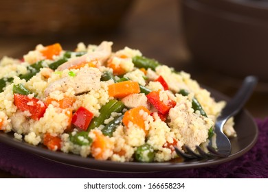 Couscous dish with chicken, green bean, carrot and red bell pepper served on plate with fork on the side (Selective Focus, Focus one third into the dish)