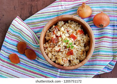 Couscous with dried apricots and fried onions in a wooden bowl. Traditional Moroccan dish. Healthy food. Top view.