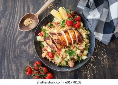 Couscous with grilled chicken breast in iron skillet