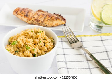 Couscous with grilled chicken and a glass of lemonade, served on different plates with table cloth and fork.