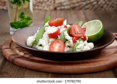 Couscous with paprika, peas and cherry tomatoes in a ceramic plate