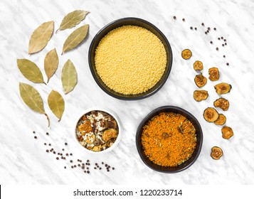 Couscous, risotto and cooking ingredients on marble background. Laurel leaves, dried zucchini and black pepper.