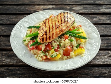 couscous salad with grilled chicken and asparagus on white plate. wooden rustic table. healthy food