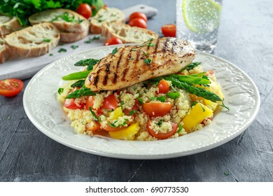couscous salad with grilled chicken and asparagus on white plate. healthy food