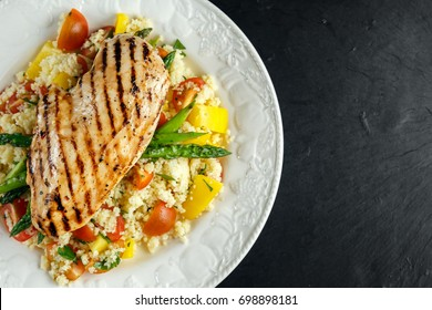 couscous salad with grilled chicken and asparagus on white plate. stone table. healthy food