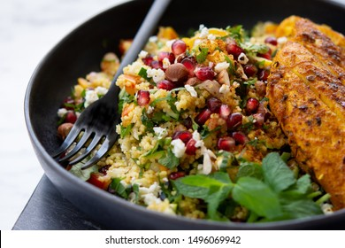 Couscous salad, tabbouleh styled, consisting of pomegranate, parsley, mint, feta cheese,  accompanied by turmeric chicken breast on a marmour serving board.