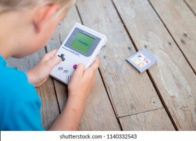 Coussac-Bonneval, France - july, 23 2018: Young kid playing on a Nintendo Gamboy.
