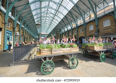 Covent Garden London England, United Kingdom - August 16, 2016: Central Piazza Convent Garden with Flowers on cart  in Foreground
