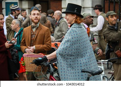 Covent Garden, London, UK - April 9 2011 : Lady participant wearing a top hat and blue country cape with her decorated vintage bike at the annual Tweed Run charity bike ride around London