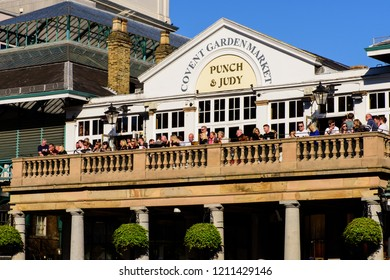 Covent Garden Market, London, England, United Kingdom - October 19, 2018: Patrons on the balcony of the Punch & Judy bar watch the buskers performing in the square