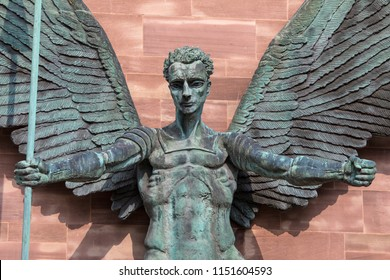 Coventry, UK - July 26th 2018: A close-up of the sculpture on the exterior of Coventry Cathedral depicting St. Michaels victory over the Devil, in Coventry, UK.