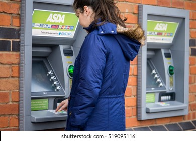 Coventry, UK - NOVEMBER 20, 2016: Young adult woman withdrew from cash machine, ASDA ATM