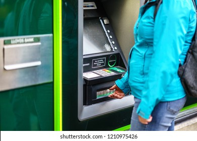 Coventry, UK - October 18, 2018: Young adult woman withdrew from cash machine, Lloyds Bank ATM