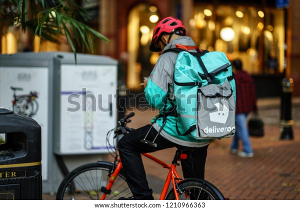 Coventry, UK - October 18, 2018 - Delivery food courier guy from Deliveroo checking order via mobile phone.