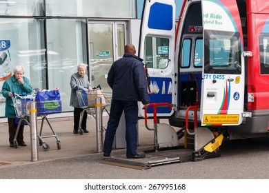 Coventry,UK - March 27th 2015: A hybrid park and ride minibus adpated to transport elderly or disabled shoppers waits for two seniors to board using the lift outside a supermarket.