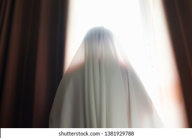 cover the body with white cloth standing at window