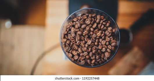 Cover image for your website. Top view of fresh roasted coffee beans in a coffee mill on a wooden table, organic coffee beans in a coffee grinder, blank space for text message