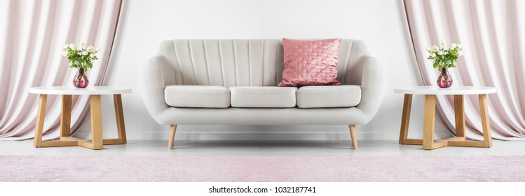 Cover photo of a beige sofa standing between two round tables with flowers in elegant living room interior