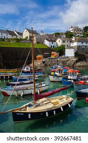 COVERACK, CORNWALL, UK - CIRCA JULY, 2015: A typical Cornish harbor and fishing village with pleasure craft and fishing boats moored in the harbour and the village of Coverack in the background.