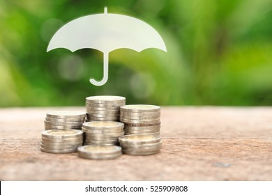 Coverage, insurance or Protection concept, Stacks and heaps of coins, umbrella nature background