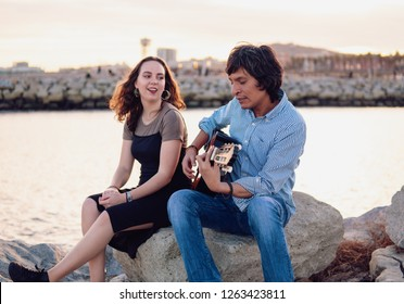 Coverband couple of musicians play acoustic guitar and sing near the beach. Sea on background